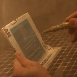 : Glass being sandblasted by fine media, inside a professional sandblasting cabinet.